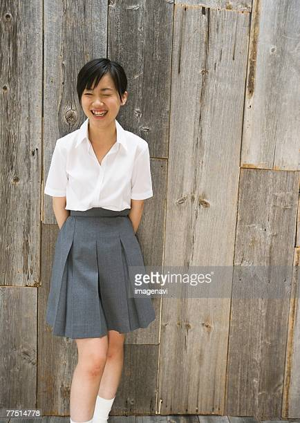 smiling teenage girl in school uniform - japanese short skirts stock photos and pictures