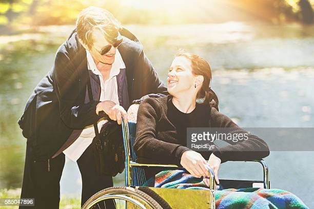 Smiling teenage girl in wheelchair with elderly caregiver at lakeside