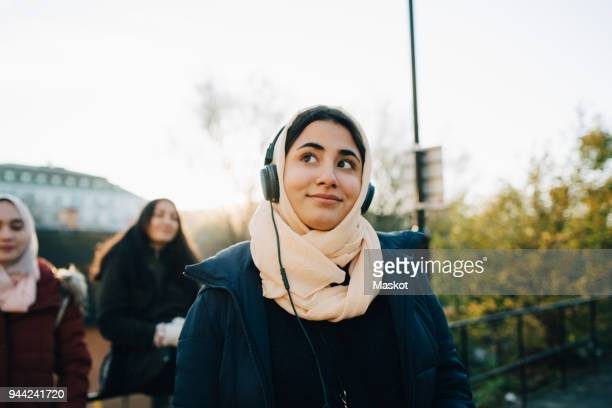 smiling teenage girl listening to headphones with friends against sky - street style stock pictures, royalty-free photos & images