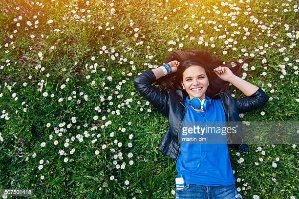 Smiling teenage girl lying down in the grass