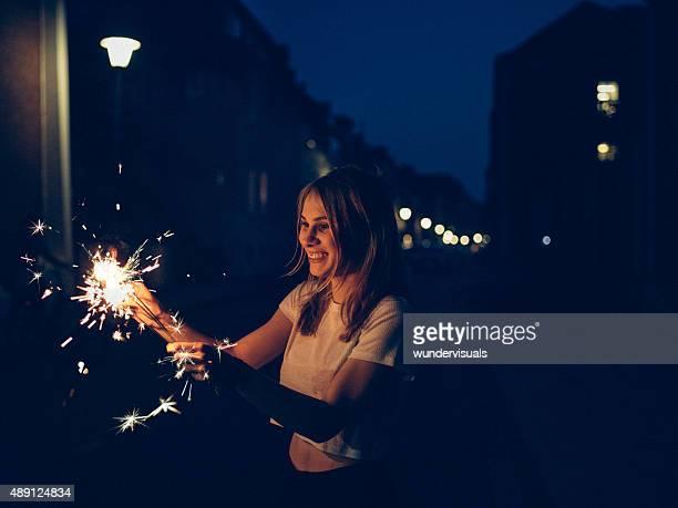 Lächelnd Teenager-Mädchen auf der Straße bei Nacht mit Wunderkerzen