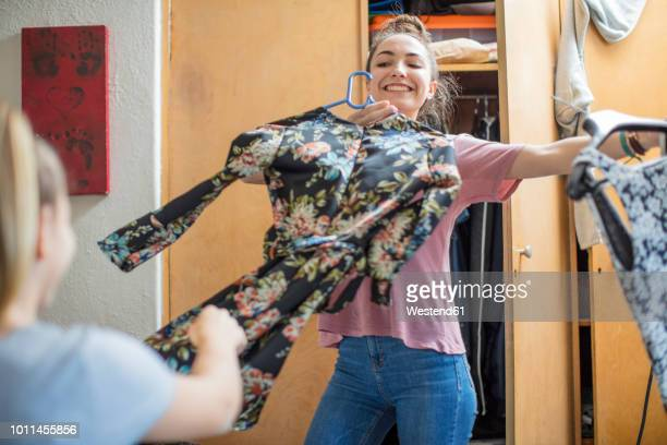 smiling teenage girl presenting clothes to her friend - kleid stock-fotos und bilder