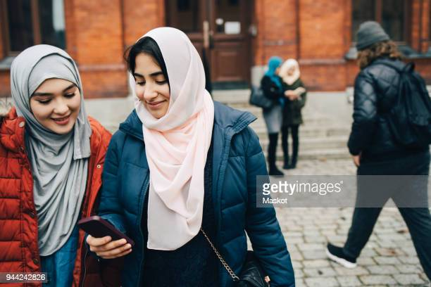 Smiling teenage girl sharing smart phone with young friend in city