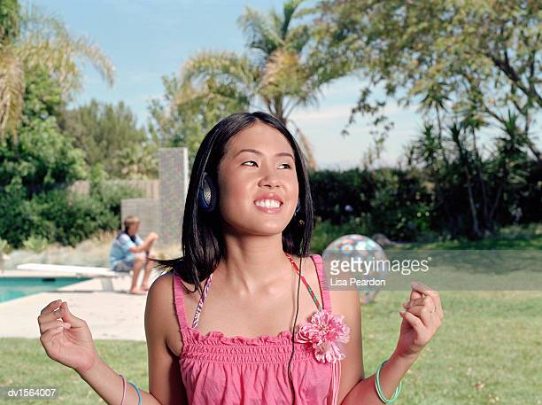 Smiling Teenage Girl Stands in a Garden Listening to Music on Her Headphones and Clicking Her Fingers