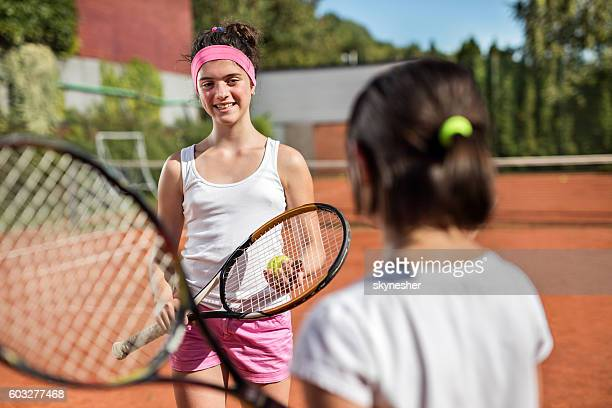 smiling teenage girl talking to a friend on tennis court. - ヘアバンド ストックフォトと画像