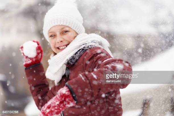 Smiling teenage girl throwing snowball - winter acitivities