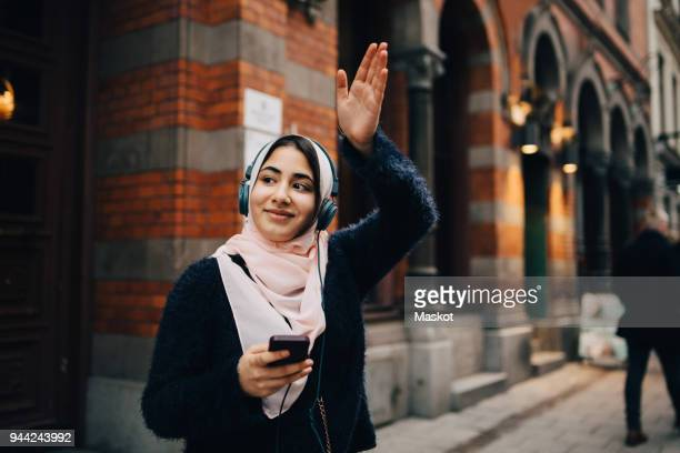 smiling teenage girl waving hand while listening to headphones on footpath in city - waving stock pictures, royalty-free photos & images