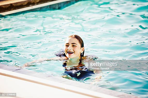 Smiling teenage girl with braces swimming in pool