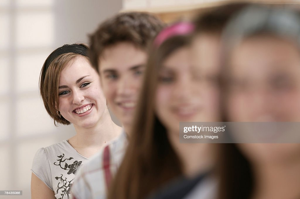 Smiling teenage girl with friends : Stockfoto