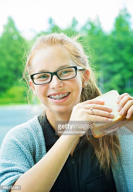 smiling teenage girl with her sandwich - beautiful girl smile braces vertical stock photos and pictures