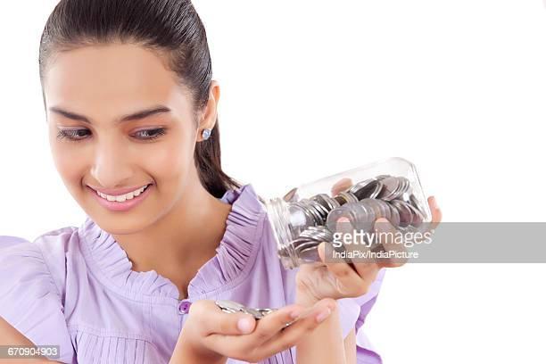 smiling Teenage Girls emptying money bank