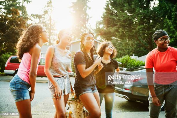 Smiling teenage girls hanging out in neighborhood on summer evening