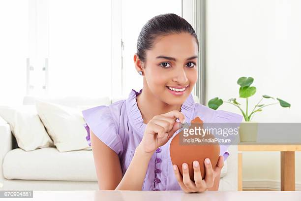 Smiling Teenage Girls Holding A money Bank In Her Hand And Dropping A Coin In The Slot