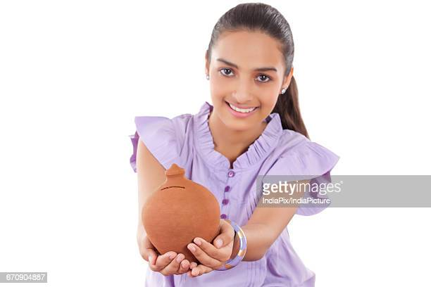 Smiling Teenage Girls Holding A money Bank In Her Hands