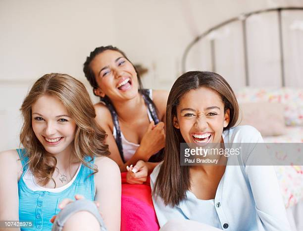 smiling teenage girls laughing in bedroom - only teenage girls stock pictures, royalty-free photos & images