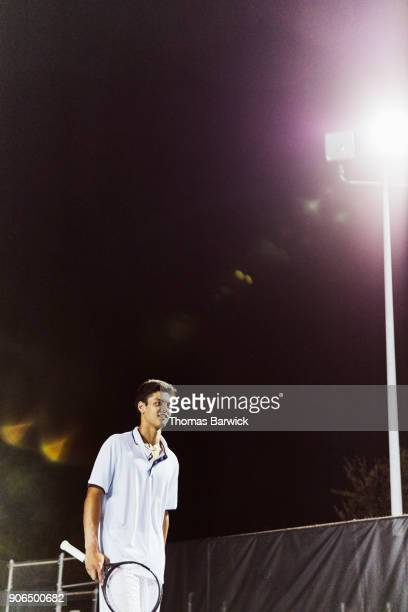 Smiling teenage male tennis player playing on outdoor court at night