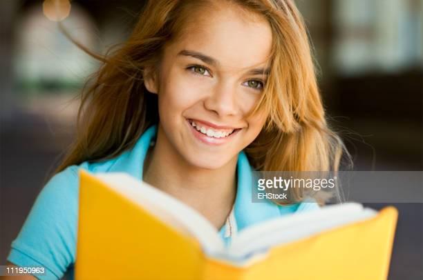 Smiling Teenage Schoolgirl With Book on School Campus