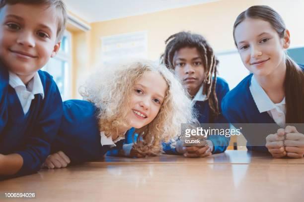 lachende teenage studenten in de klas - izusek stockfoto's en -beelden