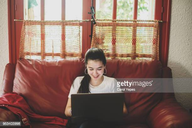 smiling teenager girl using laptop at home