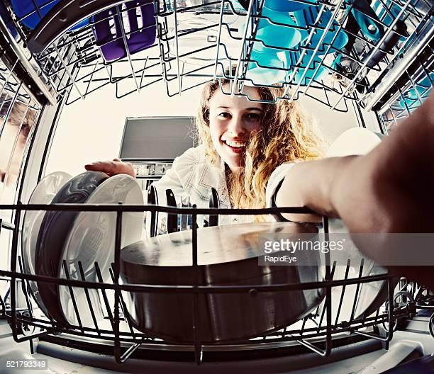 Smiling teenager helps with dishwashing  duties