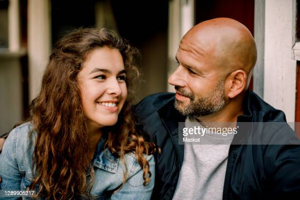 smiling teenager looking at father while talking outdoors - daughter stock pictures, royalty-free photos & images