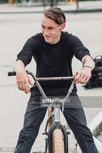 Smiling teenager sitting on bicycle at skateboard park