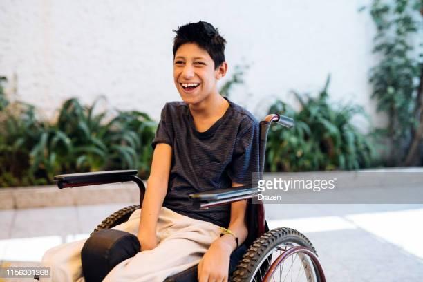 adolescente sonriente con palsy celebral en silla de ruedas - discapacidad intelectual fotografías e imágenes de stock
