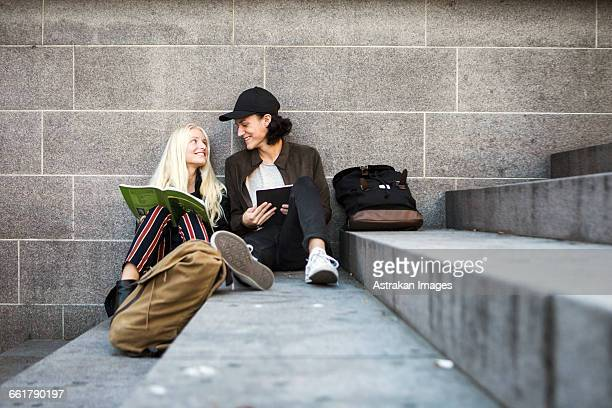 Smiling teenagers sitting on steps and looking face to face