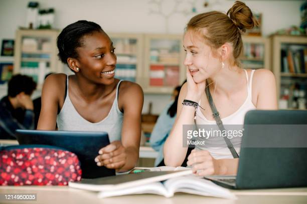 smiling teenagers talking while sitting by table in classroom - sweden stock pictures, royalty-free photos & images