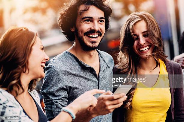 Smiling teenagers text messaging outdoors