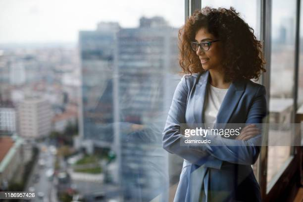 smiling thoughtful businesswoman looking through window - onward stock pictures, royalty-free photos & images