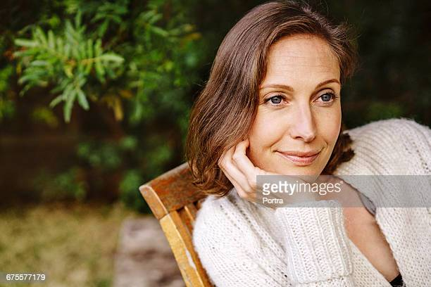 Smiling thoughtful woman sitting on chair
