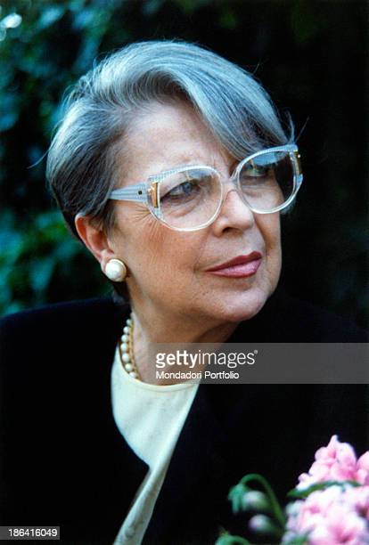 Smiling three quarter profile of the Italian actress and dubber Isa Barzizza wearing big greycoloured rimmed glasses a black blazer pearl earrings...