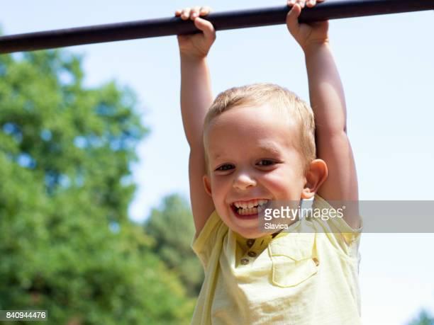 Smiling three-year-old boy having fun on the playground