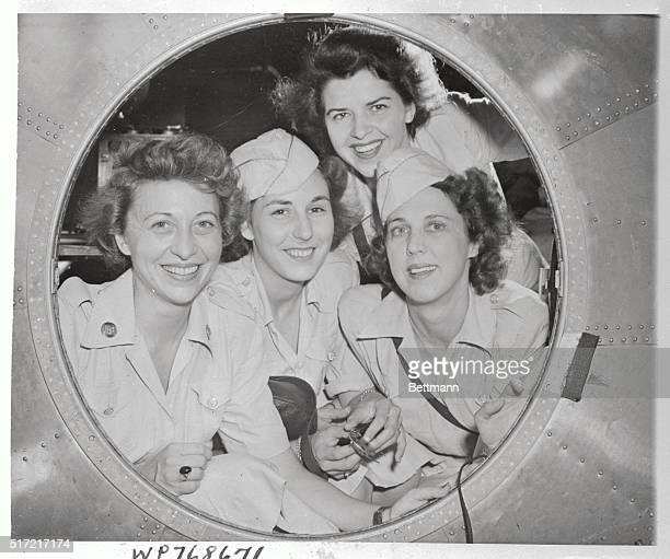 Smiling through porthole in a B-29 superfortress based at Harmon Field, Guam, are four of the first WACs assigned to the island. Left to right:...