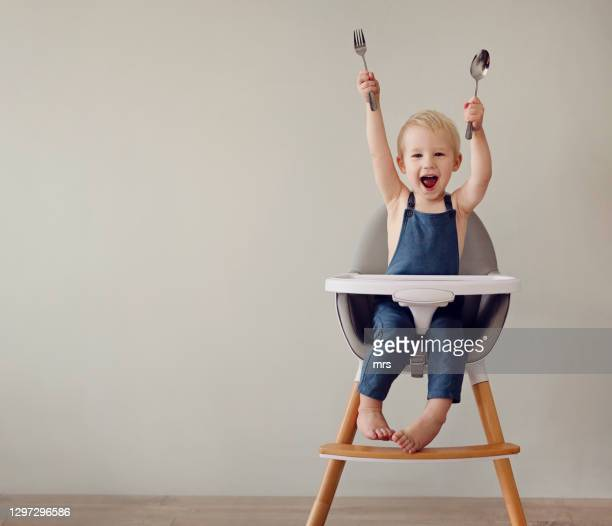 smiling toddler boy in high chair - fork stock pictures, royalty-free photos & images