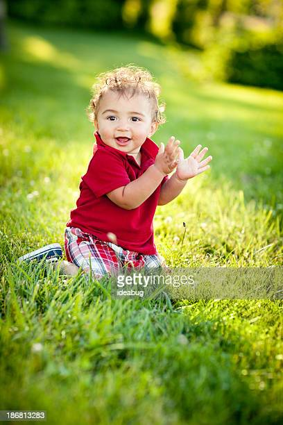 smiling toddler boy sitting in grass outside on summer day - polo shirt stock photos and pictures