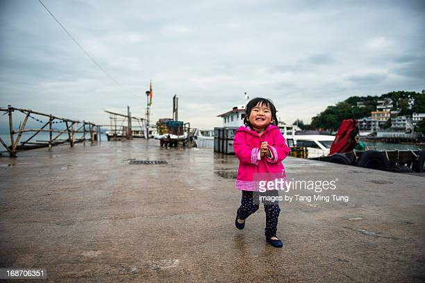 Smiling toddler girl strolling at the pier
