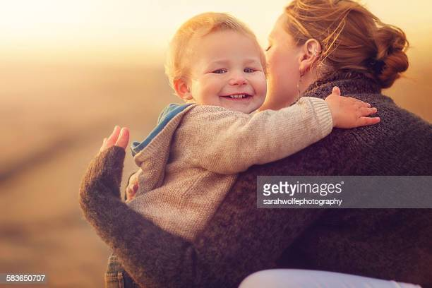 Smiling toddler giving a woman a hug