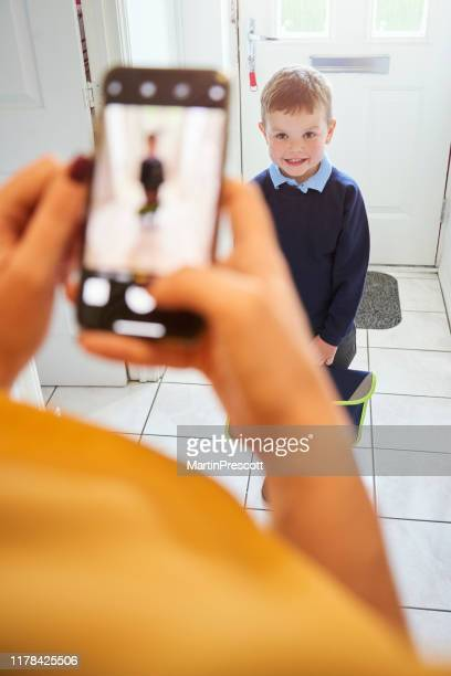 smiling toddler poses for picture in his unifrom - shoulder bag stock pictures, royalty-free photos & images