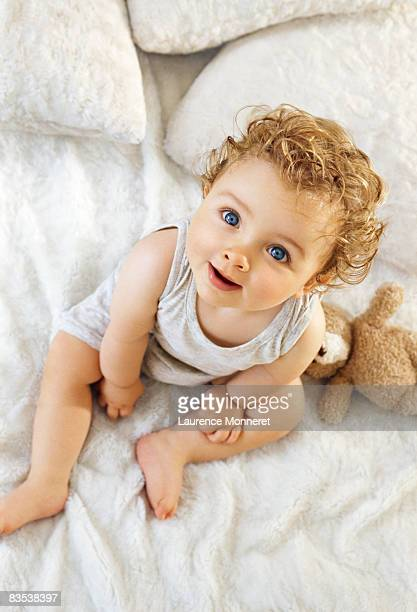 Smiling toddler raising head sat on white blanket