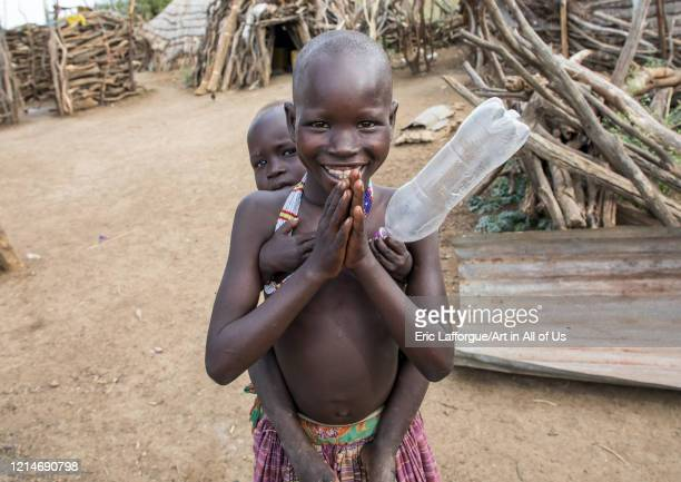 Smiling Toposa tribe girl carrying a baby in her back, Namorunyang State, Kapoeta, South Sudan on February 3, 2020 in Kapoeta, South Sudan.