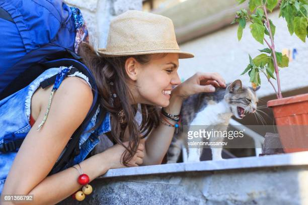 Smiling tourist caressing a cat on street