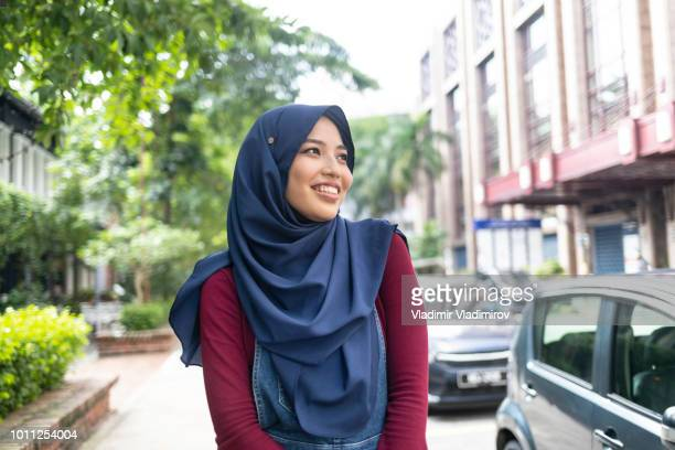 smiling tourist in the city walking on street - indonesian culture stock pictures, royalty-free photos & images