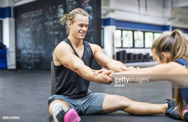 smiling trainer pulling hands of woman at gym - woman straddling man stock pictures, royalty-free photos & images