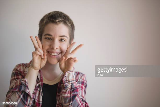 smiling transgender person making peace gesture - transgender man stock photos and pictures