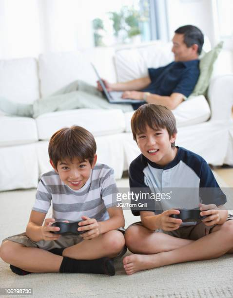 Smiling twin brothers playing video game while father uses laptop on living room sofa
