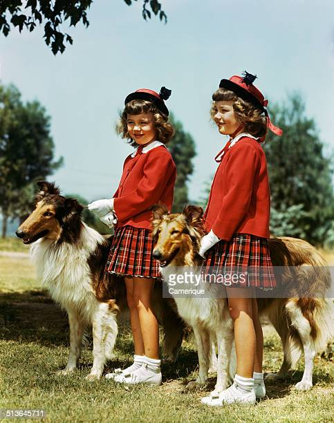 Smiling twin girls wearing matching red sweaters plaid skirts with two collie dogs Los Angeles California 1949