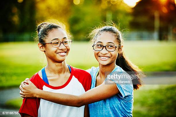 Smiling twin sisters embracing on summer evening