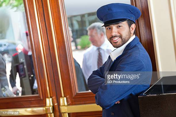 Smiling valet/doorman waiting for guests to arrive at nice hotel